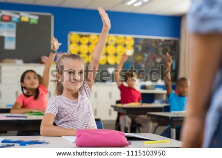 Multiethnic group of young school children raising their hands to answer a question posed by the teacher. Group of elementary kids sitting in classroom. Clever girl raising hand knowing the answer.