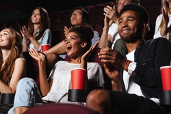 Multiethnic happy audience clapping hands while sitting at the cinema and watching movie