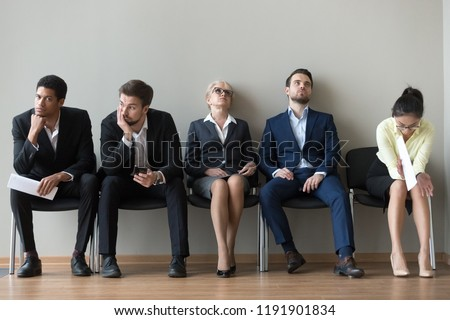 Multiethnic job candidates in queue tired of long waiting in office corridor, diverse work applicants sit on chairs feel exhausted expecting their turn for interview. Employment, hiring, HR concept
