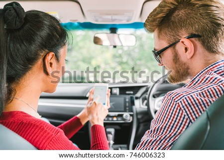 Multiethnic lover couple, white man and black Asian girl using navigator system app on smart phone in car. Modern gadget lifestyle, family travel activity, or online taxi call request service concept. #746006323