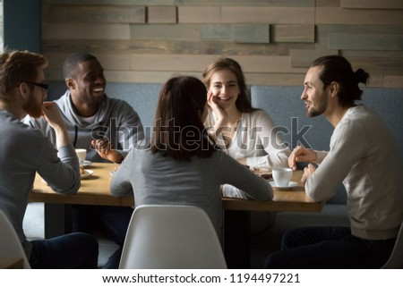 Multiethnic millennial friends sitting in café enjoying coffee laughing at jokes, diverse happy young people spend good time together having fun talking in coffeeshop. Friendship, relations concept