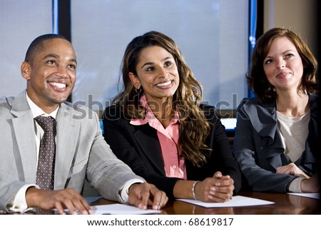 Multiethnic office workers in boardroom watching presentation, main focus on woman in middle