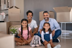 Multiethnic parents with two daughters in their new house with cardboard boxes looking at camera. Beautiful little girls sitting on floor with african mother and middle eastern dad after relocation.