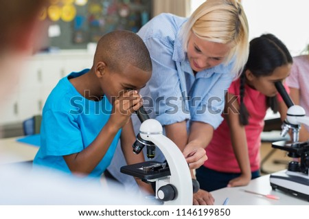 Multiethnic pupils looking through microscope at primary school. Happy elementary students in biology class analyzing cells through microscope. Children with teacher making chemical experiment. #1146199850