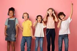 Multiethnic schoolchildren in headphones listening to music or audio books on pink background