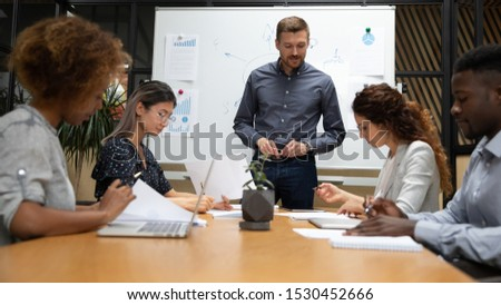 Multiethnic staff take part in educational training led by boss or coach participants do task writing solutions seated at desk in boardroom, entities before sign contract read terms conditions concept