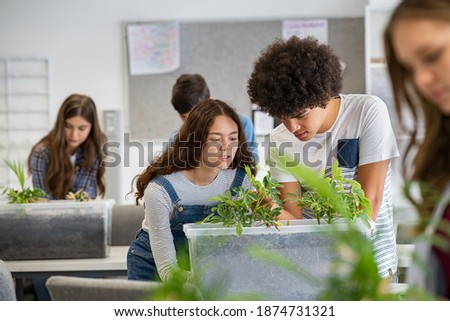 Multiethnic students analyzing plant experiment in school lab. Group of high school students in science laboratory understanding the study of roots. Classmates studying the growth of sprouts. Stockfoto ©