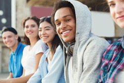 Multiethnic teen company spending time together, sitting outdoor, free space