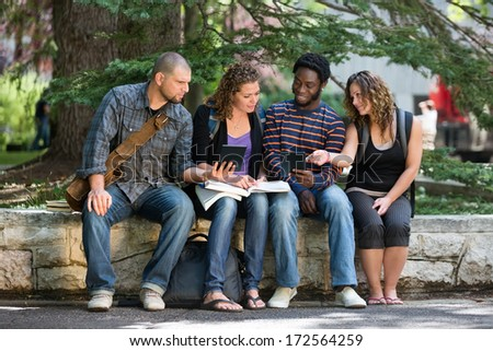 Multiethnic university students using digital tablet while studying on parapet at campus