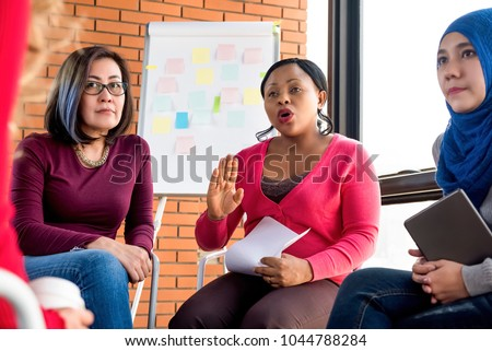 Multiethnic women in colorful casual clothes discussing in the group meeting