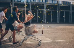 Multiethnic young people racing with shopping cart and blowing confetti. Young friends having fun on shopping carts.