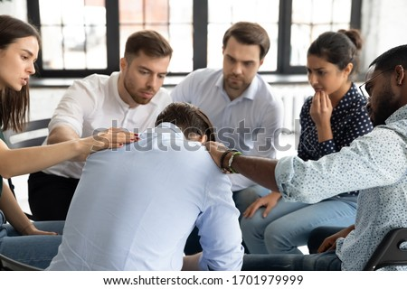 Multiethnic young people sit in circle participate in group psychological therapy together, diverse patients hug support comfort upset man patient at team counseling session, depression concept