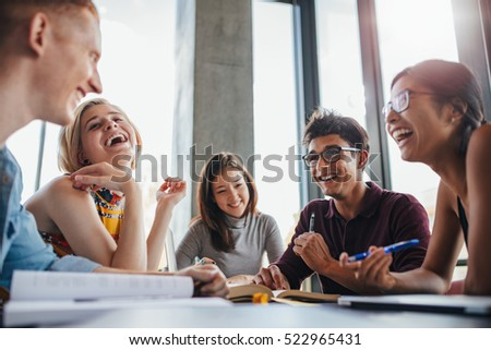 Multiethnic young people sitting at table and having fun while studying together for exams. Group of happy young students in library.