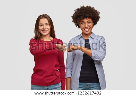 Multiethnic young women give fist bump to each other, show they are friendly team, have positive expressions, demonstrate agreement, dressed in casual clothing. Handshake and friendship concept