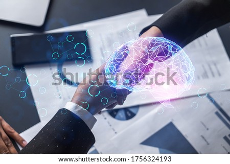 Multiexposure of two businesspeople handshake and brain hologram drawing background. Concept of data analysis. Formal wear.