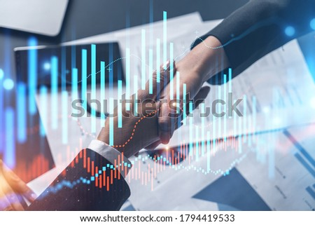 Multiexposure of two businesspeople handshake and forex graph hologram drawing background. Concept of financial market. Formal wear.