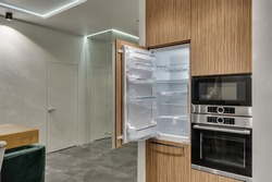 Multifunctional modern kitchen. Built-in appliances. Opened door of the new fridge