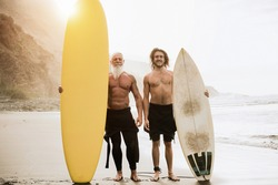 Multigeneration family having fun while surfing on beach - Focus on faces