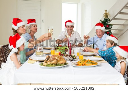 Multigeneration family toasting wine while having Christmas meal at home