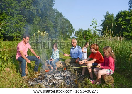 Multigenerational family cooking on campfire in field