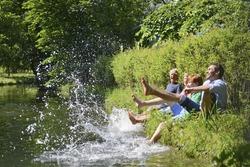 Multigenerational family splashing water from riverbank