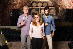 Multigenerational winery owner family standing at wine cellar. Senior winemaker and young sommelier holding a glass of red wine while businesswoman looking at camera and smiling. Small business.