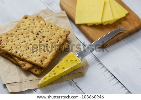 Multigrain crackers and cheese on distressed table - stock photo