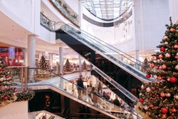 Multilevel shopping mall interior decorated with christmas trees