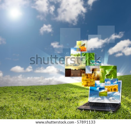 Multimedia concept with modern laptop on green field - stock photo