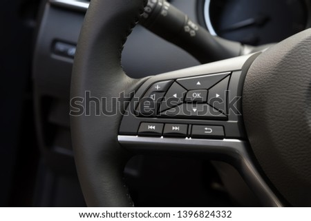 multimedia control panel  on the steering wheel of a modern car #1396824332