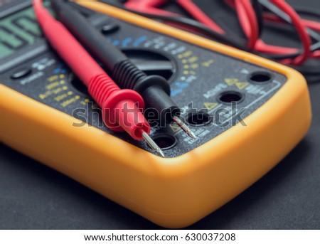 multimeter and tester on black background