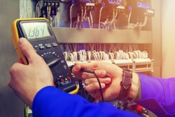 Multimeter in hands of electrician close-up against  background of electrical wires and relays. Adjustment of scheme of automation and control of electrical equipment