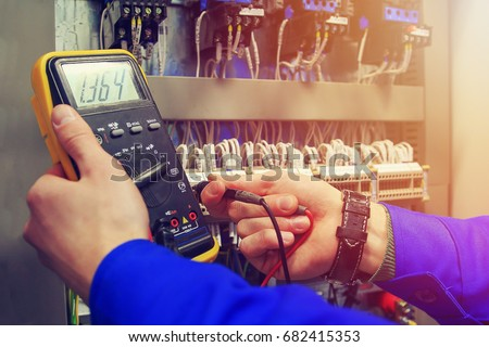 Multimeter in hands of electrician close-up against  background of electrical wires and relays. Adjustment of scheme of automation and control of electrical equipment #682415353