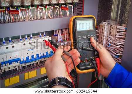 Multimeter is in hands of electrician on background of electrical automation cabinet. Adjustment of electrical control circuit for industrial equipment. #682415344