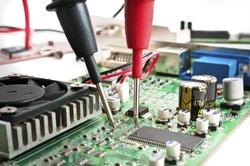 Multimeter probes examining a computer circuit board