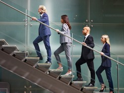 multinational and multiethnic corporate business people male and female walking up stairs in a line in modern office building.