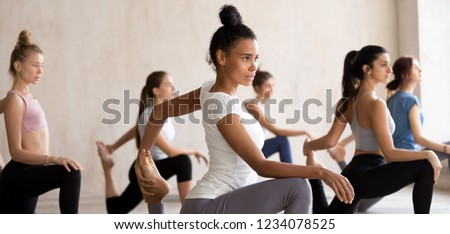 Multinational diverse young attractive sporty girls headed by mixed race coach, practising together yoga doing One Legged King Pigeon pose stretches body. Horizontal photography banner for website