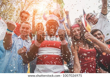 Multinational football supporters celebrating the begin of world competition - Happy multiracial people having fun together outside of stadium - Main focus on black man - Sport and bonding concept - Shutterstock ID 1007026975