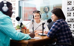Multinational group of cheerful friendly smiling young adults emotionally discussing in radio studio