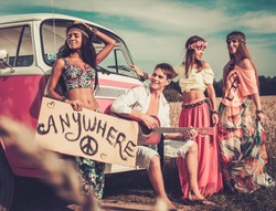 Multinational hippie hitchhikers with guitar and luggage on a road