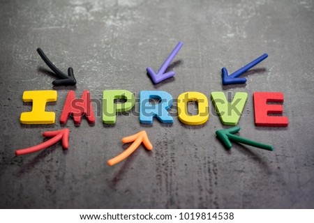 Multiple arrow pointing to colorful alphabet word IMPROVE at the center on dark black cement wall background, self improvement motivation concept.