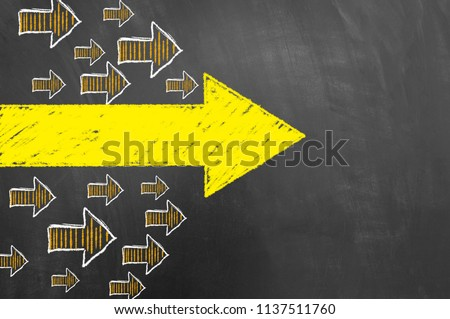 Multiple arrows yellow chalk drawing on blackboard or chalkboard as direction orientation trend pointer concept with copy space