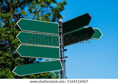 Multiple blank green arrow shaped directional street signs on a pole pointing in various directions #1164116467