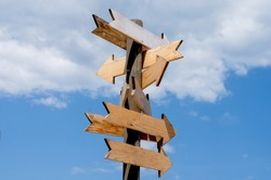 Multiple blank wooden arrow signposts on wood  pole agains blue sky  .