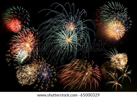 Multiple bursts of multicolored fireworks fill the frame against a black background
