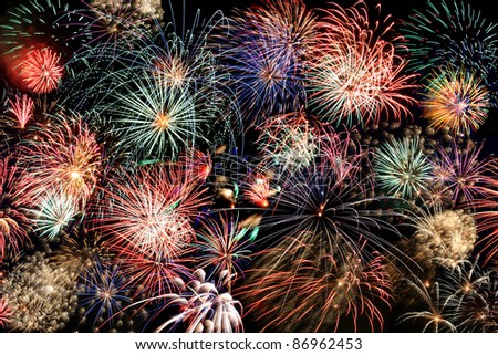 Multiple bursts of multicolored fireworks fill the horizontal frame against a black background