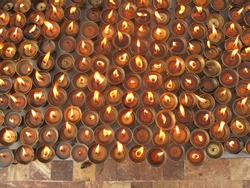 multiple candle flames on tiled background