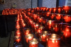 Multiple candles lit in red candle holders. Many candles glowing bright and warmly at a catholic church. Close up and low angle view of meditative candles spread an ambient light.