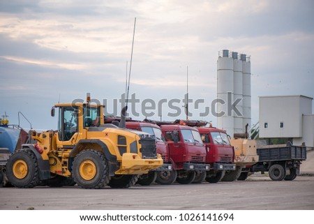 Multiple cars, trucks, loaders, concrete mixers and construction machinery in large parking lot in industrial territory, next to concrete and asphalt factory