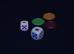 Multiple Colored Dice in a dark background. Dice are small, throwable objects with marked sides that can rest in multiple positions. They are used for generating random numbers used in board games